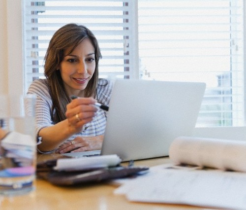 Woman working on laptop in home office.