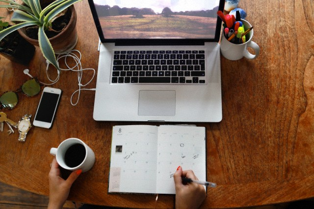 Person writing in diary with laptop on desk