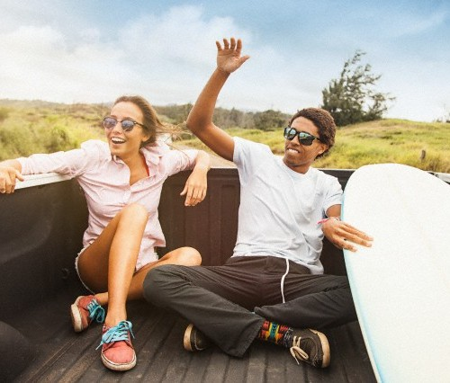 Portrait of young couple riding on back of pickup truck